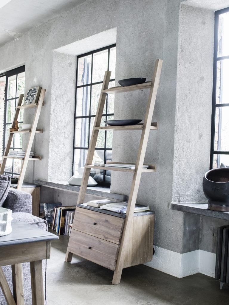 Bibliothèque à pan coupé apposée contre le mur comme une échelle, elle est en bois clair et plateau béton