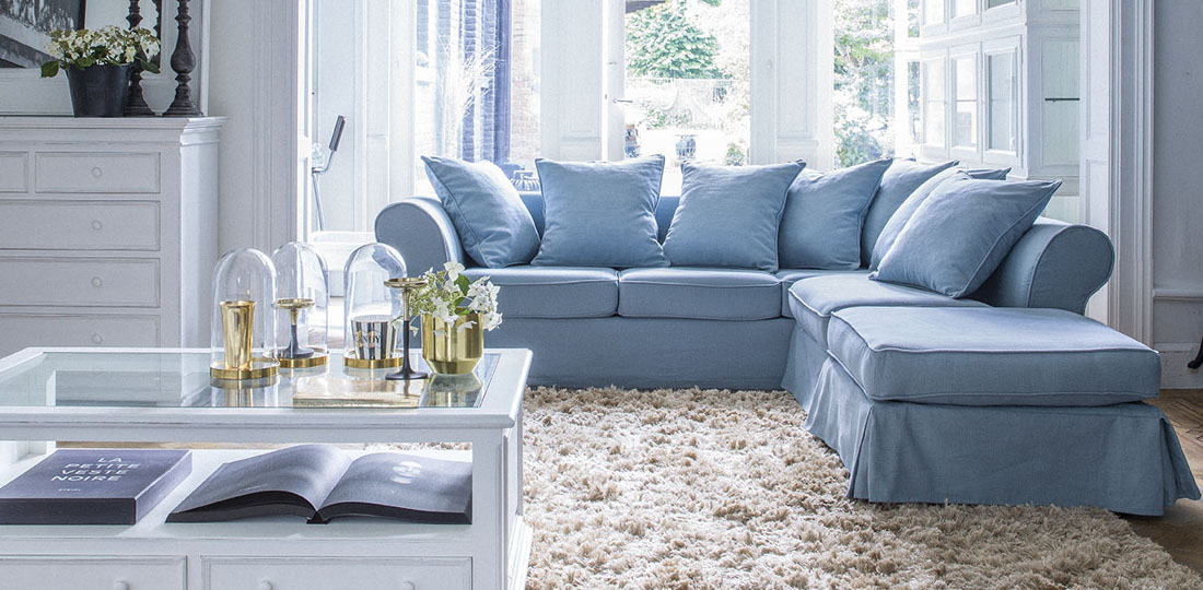 salon avec grand canapé d'angle en lin bleu avec jupe