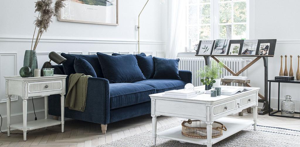 salon style Directoire avec table basse et bout de canapé blanc et canapé en velours bleu paon